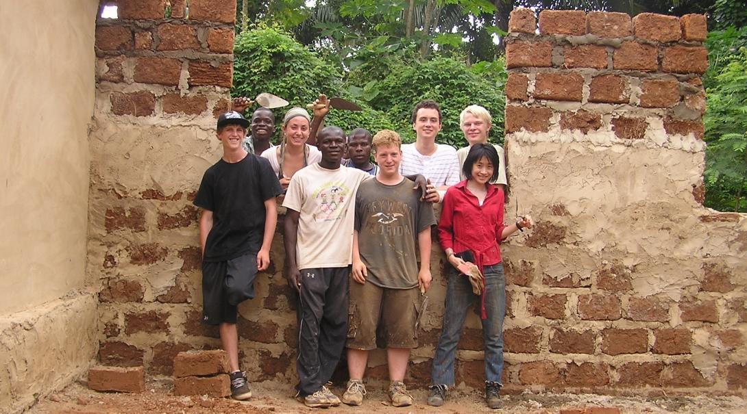 Volunteers take a photo by their building work on the service learning project in Ghana for middle school students.